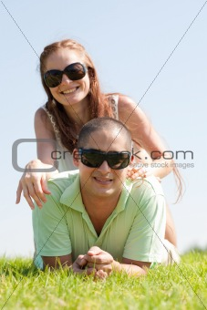 beautiful young Couple lie down on grass