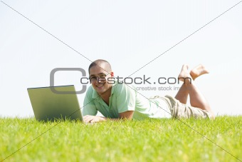 A young men lying on the in the park using a laptop