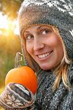 Pretty young woman holding a pumpkin