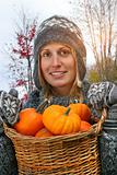 Young woman holding a basket full of pumpkins