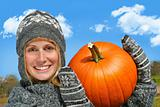 Young woman holding up a  pumpkin