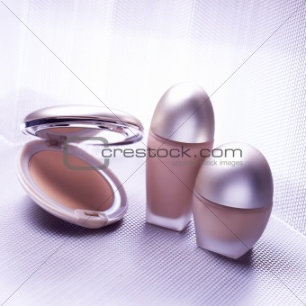 Three cosmetic objects on metallic background