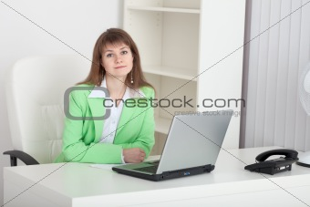 Beautiful young girl - manager sits at a table in office