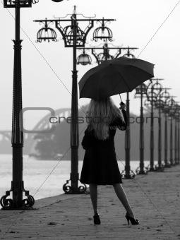 Blonde with umbrella on promenade
