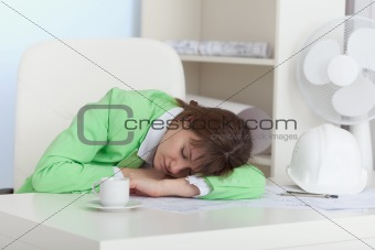 Girl sleeps on table at office in working hours