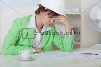 Tired woman - engineer in helmet sits at table in office