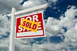Sold For Sale Real Estate Sign on Cloudy Sky.