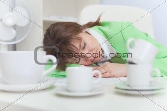 Beautiful woman sleeps on workplace with coffee cups