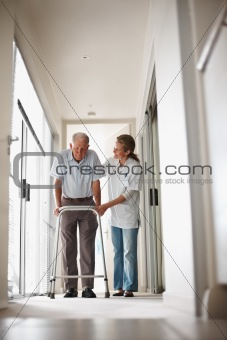 Doctor helping a senior man on a walker at the corridor