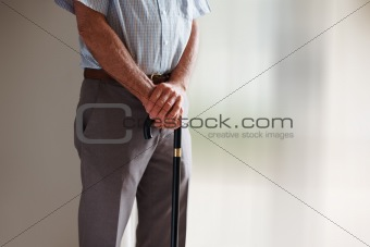 Mid section of a senior man with his walking stick