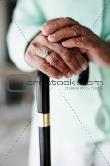Closeup focus of a senior woman's hand on a walking stick