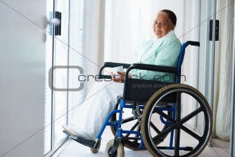 Elderly woman having coffee while on a wheel chair , smiling