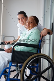Happy retired woman on the wheel chair with a nurse