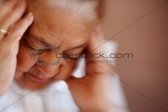Closeup of an old woman having a severe headache