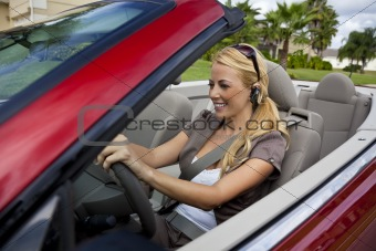 Beautiful Young Woman Driving Convertible Car Talking on Bluetoo