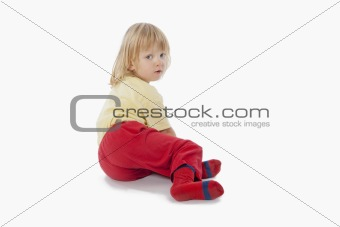 boy with long blond hair sitting on the floor-clipping path