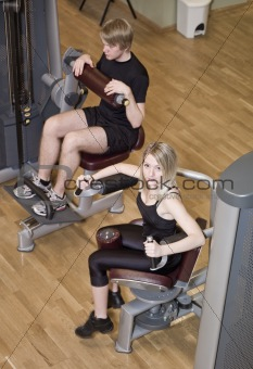Boy and a girl using excercise machines