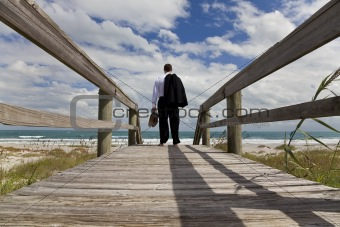Businessman Standing Barefoot Looking Across A Beach To The Sea