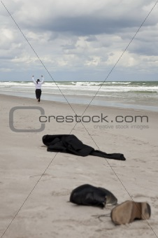 Businessman Leaving Clothes On Beach and Running Towards The Sea