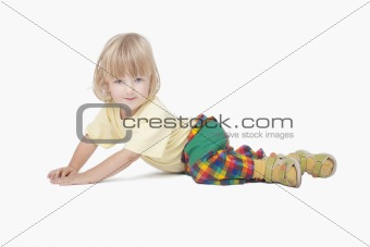boy with long blond hair lying down, looking at camera - clipping path