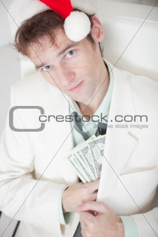 Businessman in white suit and Christmas cap hides money in pocke