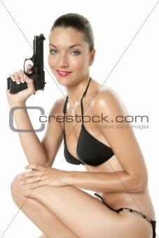 Beautiful sexy woman with black bikini and gun