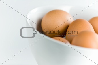 Fresh brown eggs in white bowl