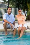 Happy African American Couple Sitting With Feet In Swimming Pool