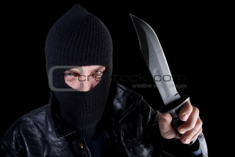 Man in mask with large knife on black