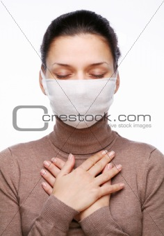 Young woman in medical mask keeping hands on chest
