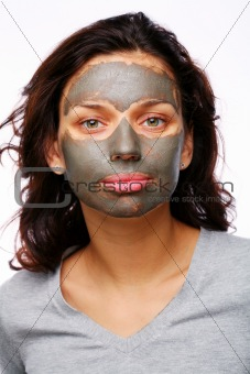 A funny girl with  mud mask on a white backgroung