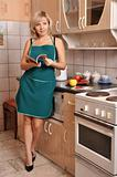 The housewife in green apron on kitchen
