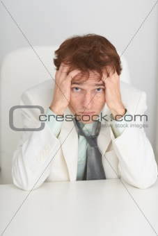 Sad young businessman sits at a table