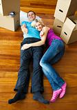 Young couple sleeping on the floor with boxes around. Moving house