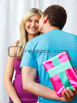 Boyfriend giving a present and a kiss to his girlfriend