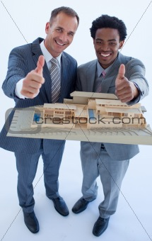 Architects holding a model house with thumbs up