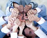 Close-up of business team on floor in a circle with thumbs up