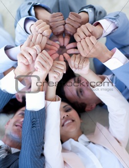Business team on floor in a circle with thumbs up