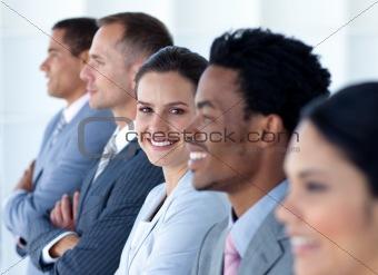 Five businesspeople standing in corridor smiling
