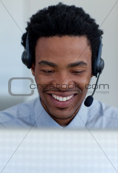 Smiling Afro-American businessman talking in a call center
