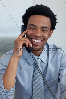 Portrait of smiling Afro-American businessman on phone in office