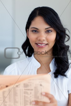 Beautiful businesswoman reading a newspaper
