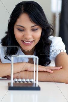 Businesswoman looking at kinetic balls