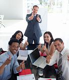 Business team in a meeting with thumbs up