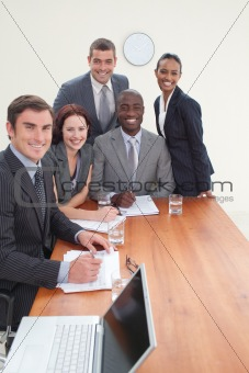 Five business people in a meeting smiling at the camera