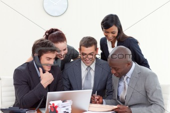 Business people in a meeting  using a telephone and a laptop