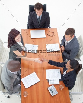 High angle of businesswomen shaking hands in a meeting