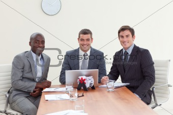 Three businessmen in a meeting smiling