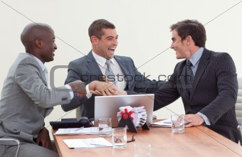 Three businessmen in a meeting celebrating a success