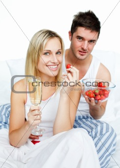 Couple celebrating an engagement with strawberries and champagne